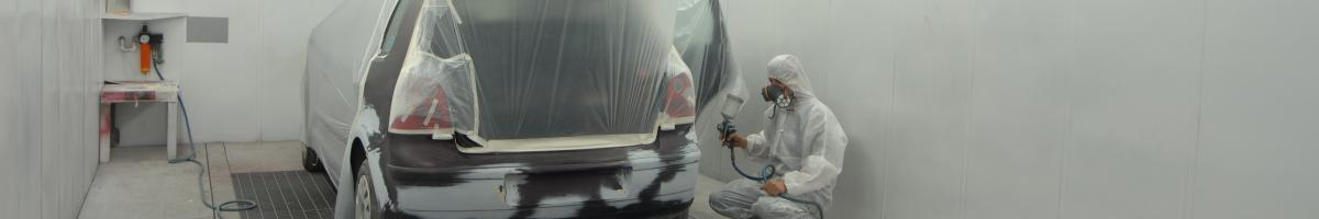 man painting car in spray booth