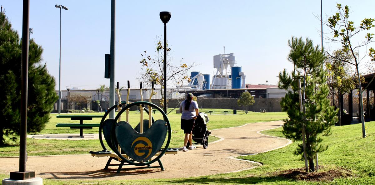 parent pushing a stroller on track at park in South Los Angeles