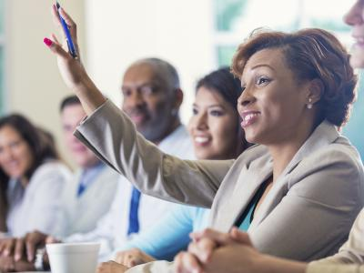 Woman raising hand in meeting