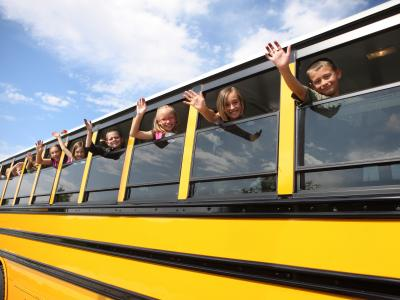 children on school bus waving out windows
